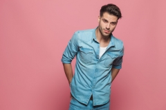 seductive man wearing denim shirt with hands behind his back