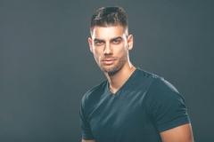Handsome man posing in studio on dark background