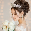 Wedding Hairstyle in a short dress with lace in the crown earrings. Wedding bouquet