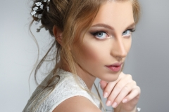 Pretty bride with beautiful elegant hairstyle, isolated on a gray background.